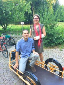 Joakim Couroud et Marie Schwebel, de l'association Bretz'selle, qui promeut l'utilisation du vélo à Strasbourg, posent dans la remorque à assistance électrique, fabriquée par la société allemande Carla, qui serait utilisée pour les collectes de biodéchets. (Photo EB - Les Défricheurs)