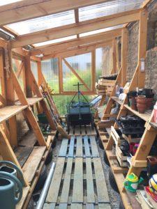 La serre, construite à côté de la terrasse, sert à la fois de pépinière, d'abri de jardin pour ranger les outils, et de bar lors des soirées organisées à L'Arrosoir. (Photo EB - Les Défricheurs)